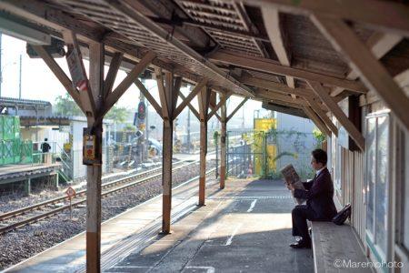 ホームの長椅子に座って新聞を読むサラリーマン