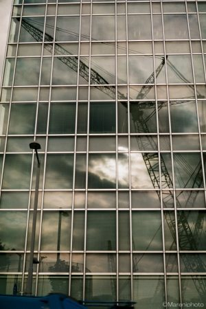 ビルに映る曇り空とクレーン