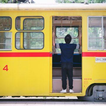 昔の都電の車内を見上げる人