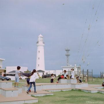 灯台の前の広場の家族連れ