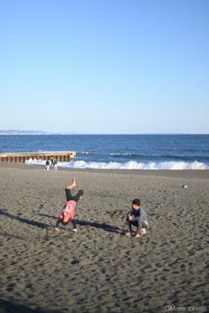 砂浜で宙返りする少年