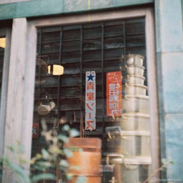 窓に映り込んだ板塀と看板