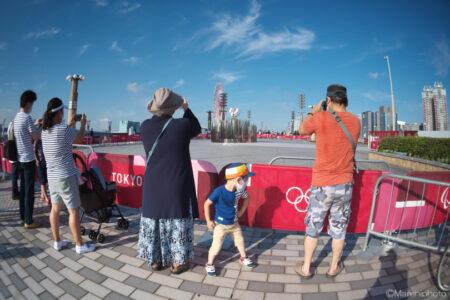 聖火台の写真を撮る人とオリンピックマークを眺める子供